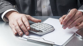 Businessman with calculator and holding a pen for risk management Stock Photo
