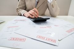 Businessman with calculator and unpaid bills Stock Images