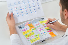 Businessman With Calendar And Diary. Close-up Of Businessman With Calendar Writing Schedule In Diary Stock Images