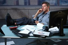 Businessman on call feet up on office desk royalty free stock photos