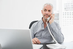 Businessman on call in front of laptop at office desk Royalty Free Stock Photography
