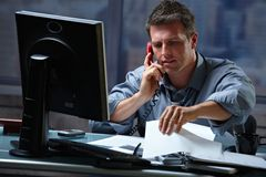 Businessman on call in overtime Royalty Free Stock Photo