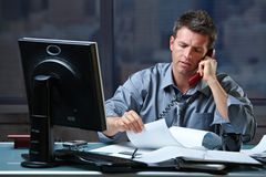 Businessman on call in overtime stock photo