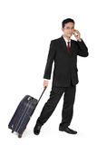 Businessman on call pulling travel bag Stock Images