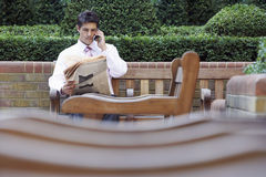 Businessman On Call While Reading Newspaper In Park Royalty Free Stock Images