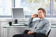 Businessman on call sitting at desk looking up Royalty Free Stock Image