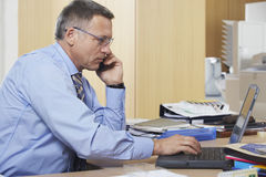 Businessman On Call While Using Laptop At Desk Royalty Free Stock Images