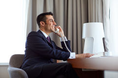 Businessman calling on desk phone at hotel room Royalty Free Stock Photography