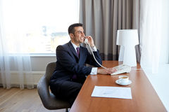 Businessman calling on desk phone at hotel room Royalty Free Stock Image