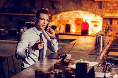 Businessman calling his partner while working remotely in the bar. Businessman calling. Businessman wearing glasses calling his partner while working remotely in stock photo