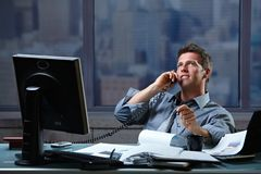 Businessman calling on landline at office. Mid-adult successful smiling businessman calling on landline listening to conversation sitting at office desk Stock Images