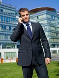 Businessman Calling Through Phone Outside Building Royalty Free Stock Images