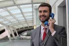 Businessman calling by public phone at the airport stock image