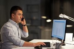 Businessman calling on sartphone at night office royalty free stock photography