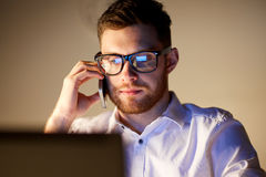 Businessman calling on smartphone at night office. Business, overwork, people, deadline and technology concept - businessman in glasses with laptop computer Royalty Free Stock Photos