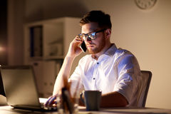 Businessman calling on smartphone at night office. Business, overwork, people, deadline and technology concept - businessman in glasses with laptop computer Royalty Free Stock Photography