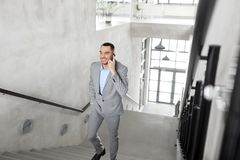 Businessman calling on smartphone at office. Business people, technology and corporate concept - businessman calling on smartphone at office Stock Images