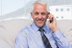 Businessman calling on smartphone and smiling at camera Stock Photos