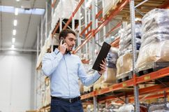 Businessman calling on smartphone at warehouse Royalty Free Stock Images