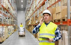 Businessman calling on smartphone at warehouse. Logistic business, technology and shipment concept - businessman calling on smartphone at warehouse Stock Photo