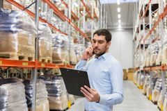 Businessman calling on smartphone at warehouse. Wholesale, logistic business, technology and people concept - businessman calling on smartphone at warehouse Stock Image