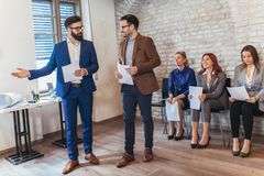 Businessman with candidate for job interview. Businessman with candidate next to people waiting for job interview in a modern office royalty free stock photography