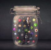 Businessman captured in a glass jar with colourful app icons con Royalty Free Stock Photo