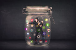 Businessman captured in a glass jar with colourful app icons con Royalty Free Stock Images