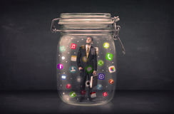 Businessman captured in a glass jar with colourful app icons con Royalty Free Stock Image