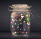 Businessman captured in a glass jar with colourful app icons con royalty free stock photography