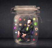 Businessman captured in a glass jar with colourful app icons con Stock Photo
