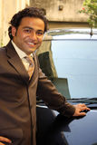 Businessman with Car. An Indian businessman posing near his black car Royalty Free Stock Photography