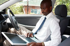 Businessman in a car. A businessman inside a car with laptop Stock Photography