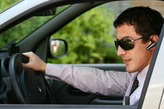 Businessman in car with blue-tooth. Businessman driving a car with blue-tooth hands-freeand sunglasses stock photography