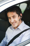 Businessman in car with bluetooth. Smiling businessman driving a car with bluetooth hands-free stock image