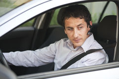 Businessman in car with bluetooth. Businessman driving a car with blue-tooth hands-free stock image