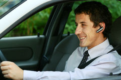 Businessman in car with bluetooth. Smiling businessman driving a car with blue-tooth hands-free royalty free stock photo