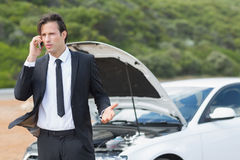 Businessman after a car breakdown Stock Images