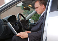 Businessman in car checking email on his laptop Stock Photo