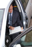 Businessman in car checking email on his laptop Stock Photography