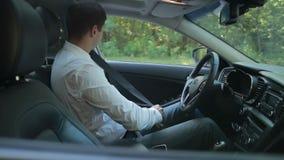 Businessman in car fastening seatbelt stock video footage