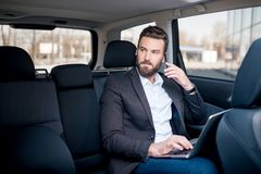 Businessman in the car. Handsome businessman talking with phone sitting with laptop on the backseat of the car Stock Photo