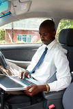 Businessman in a car with laptop. An african businessman inside car with laptop royalty free stock image