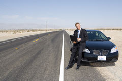 Businessman by car on open road in desert, using laptop computer, portrait Royalty Free Stock Images