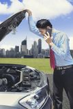Businessman with car trouble calling for a help. Businessman calling for a help using a mobile phone while checking on the engine Stock Image