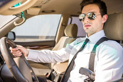 Businessman in the car. Young confident  businessman  in sunglasses with gun sitting in his luxurious car Stock Photography