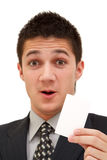 Businessman with card. A young happy businessman shows a white business card to us Royalty Free Stock Photos