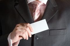 Businessman with Card. A businessman holding a blank business card Royalty Free Stock Photos