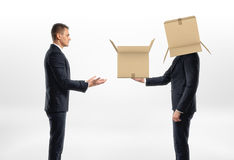 Businessman with cardboard box on his head passed another one to man Royalty Free Stock Image