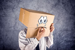 Businessman with cardboard box on his head and sad face expressi Royalty Free Stock Photo